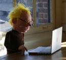 Nerd puppet working on his Macbook